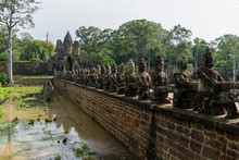 Sculptures Lining A Bridge That Leads To One Of The Gates Of The Angkor UNESCO World Heritage Site