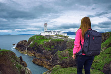 Girl With A Backpack Looking The Fanad Head Lighthouse In Ireland
