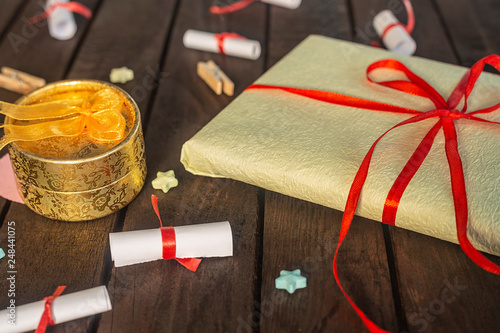 Romantic background. Gift box with rolled wishes paper gift pack on wooden board.