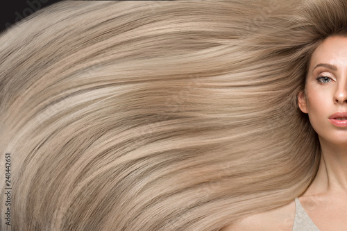 Fototapeta  Beautiful blond girl in move with a perfectly smooth hair, and classic make-up