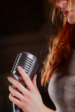 Hands Of The Singer Holding A Large Shiny Metal Microphone On A Black Background. A Place For A Label, Copy Space For Text