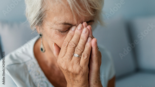 Obraz na plátně Portrait of an attractive senior woman sitting on a sofa at home with a headache, feeling pain and with an expression of being unwell
