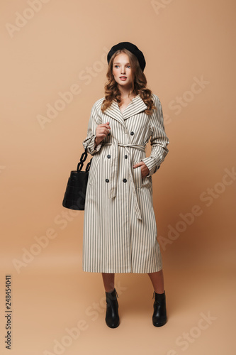 Fotografía  Young attractive woman with wavy hair in striped coat and black hat holding bag