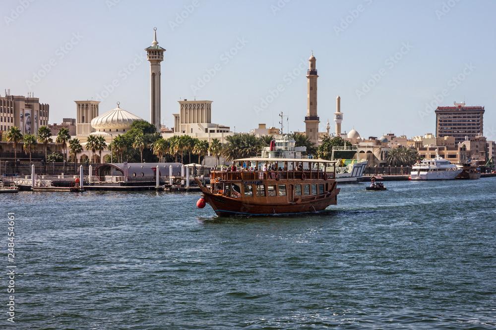 Fototapeta Dubai, UAE: Tourist boat abra on canal of Dubai Creek old tow