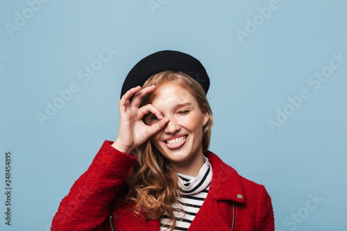 83a32b5e87232 Close up beautiful smiling girl with wavy hair in black beret and red  jacket playfully showing tongue while looking in camera over blue background