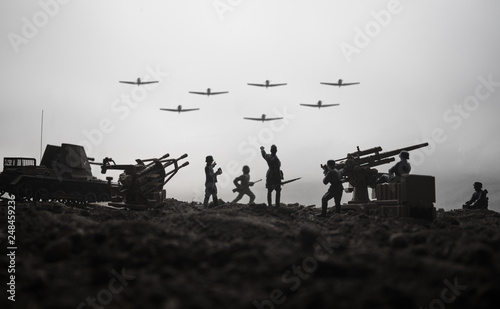 Tela An anti-aircraft cannon and Military silhouettes fighting scene on war fog sky background