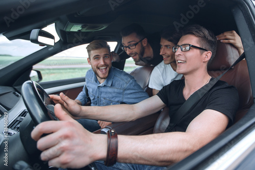 side view . friends sitting in the car and looking at the camera. Canvas Print