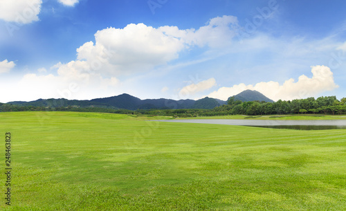 Fényképezés  Golf course with Green grass and trees in beautiful park under the blue sky