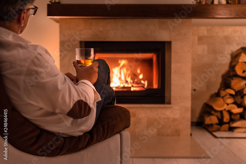 Fotografia Man sitting at home by the fireplace and drinking a whiskey.