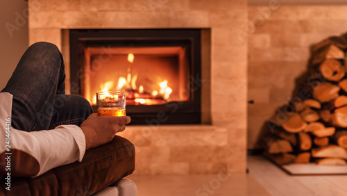 Fotografía  Man sitting at home by the fireplace and drinking a whiskey.