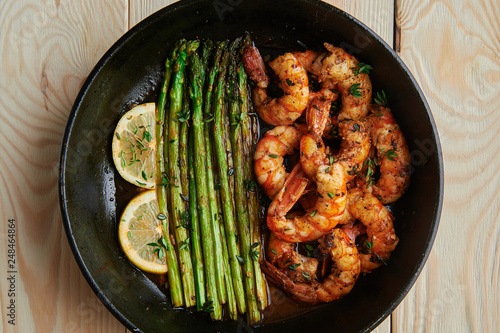 Fototapeta fried langoustines with asparagus decorated with lemon slices. roasted king prawns tiger shrimps with green garnish obraz