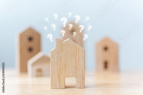 Obraz Real estate developer and managing property investment concept. Selective focus wooden houses with question mark on table - fototapety do salonu