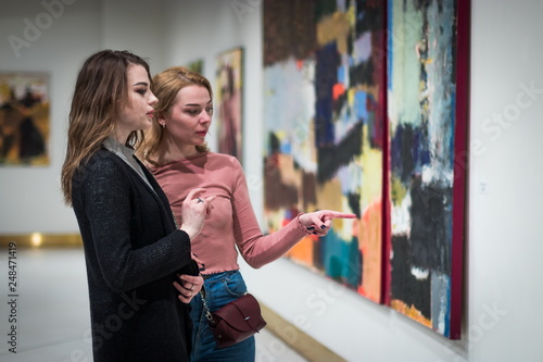 Fotografía  two girls discuss paintings in Gallery of modern art