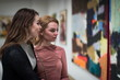 Leinwanddruck Bild - two girls discuss paintings in Gallery of modern art