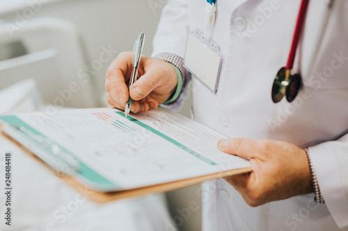 Fotografia  Physician noting down symptoms of a patient