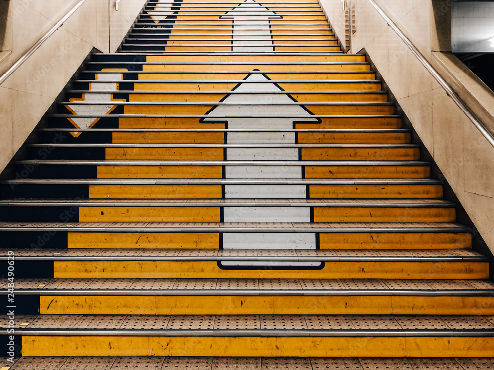 Fototapeta Big arrows direction symbol on concret stair in subway in Japan. there is seperate the walk way clearly. Line up and down.