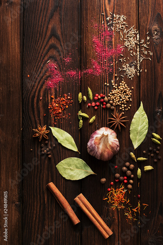 Fotografía  A variety of spices on a wooden brown plank background, peppercorns, bay leaves, garlic, star anise, cinnamon, cardamom, zira, sumac, coriander