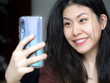 Image of excited Asian Chinese Thai Filipino beautiful happy young woman make selfie by camera at home, Adorable happy glad to see friend, family making video call by Internet.
