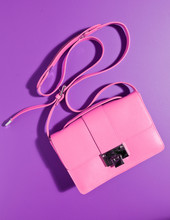 A Beautiful Expensive Womans Pink Leather Handbag Against A Complimentary Purple Coloured Background With The Bag Strap Floating In The Air. Creative Product Photography.