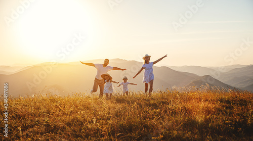 Poster Hoogte schaal Happy family: mother, father, children son and daughter on sunset