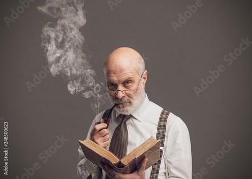 Fotografering  Senior academic professor reading and smoking a pipe