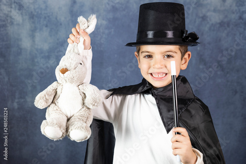 Foto Little magician doing a trick with a rabbit