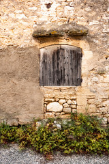 Fototapeta na wymiar stone wall with old wood closed window