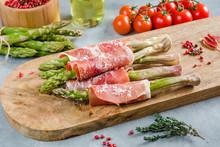 Fresh Organic Asparagus Wrapped In Prosciutto Ham On A Cutting Board.