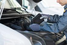 Car Mechanic Putting Oil In A ...