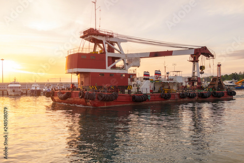 Fotografia  Large barge with a powerful crane in the port