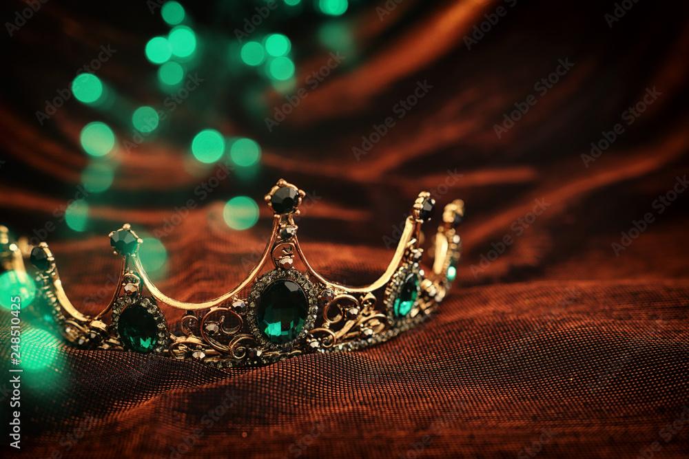 Fototapeta photo of gold crown over gothic dark silk background. Medieval period concept.