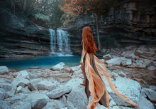 Charming Red-haired Girl Stands On Coast Of Clear Cold Clear Lake, Brilliant Magical Water Of Waterfall In Georgia, Lady In Long Green Elegant Flying Dress Walks Over Stones, Martvili Canyon Nature