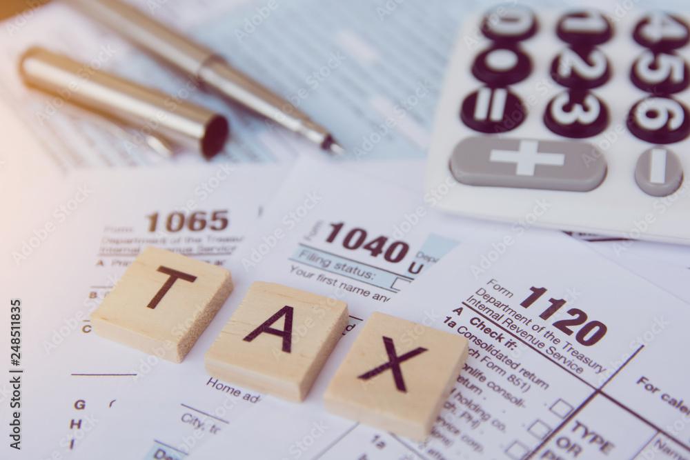 Fototapeta Tax season with wooden alphabet blocks, calculator, pen on 1040 tax form backgrounda