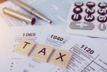 Tax Season With Wooden Alphabet Blocks, Calculator, Pen On 1040 Tax Form Backgrounda