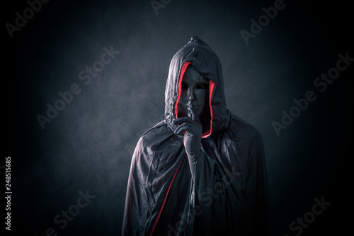 Photo  Scary figure with black mask in hooded cloak