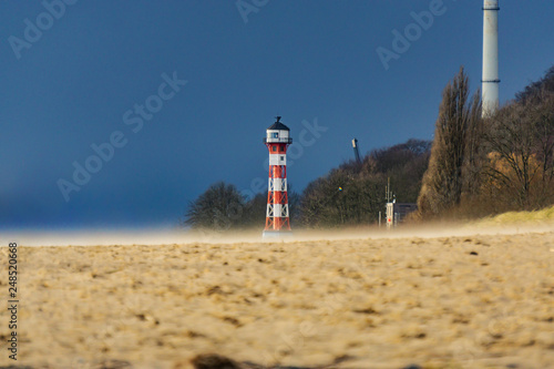 Strum in Hamburg - Am Elbstrand mit Leuchtturm Fototapeta