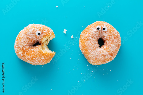 Fotografia Funny doughnuts with eyes, cartoon like characters, on blue background