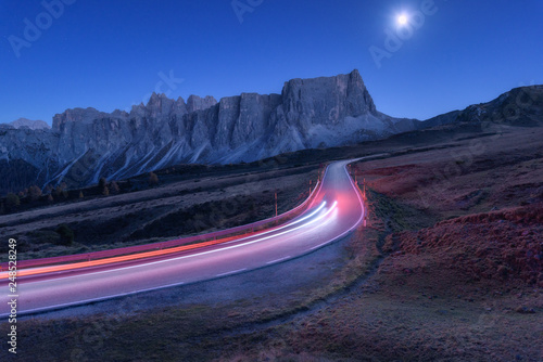 Canvas Prints Night blue Blurred car headlights on winding road at night in autumn. Landscape with asphalt road, light trails, mountains, hills, blue sky with moonlight at dusk. Roadway in Italy. Moon over highway and rocks