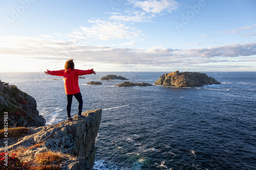 Obraz na plátně Woman in red jacket is standing at the edge of a cliff with open arms and enjoying the beautiful ocean scenery