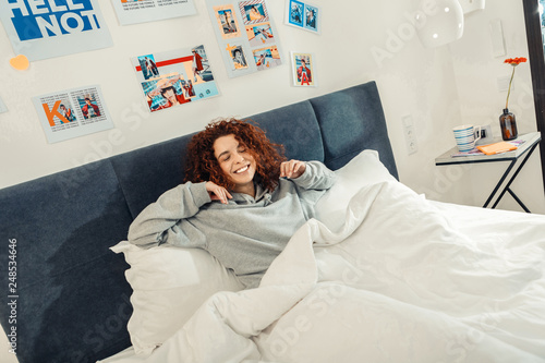 Photo  Curly red-haired woman feeling cheerful waking up in the morning