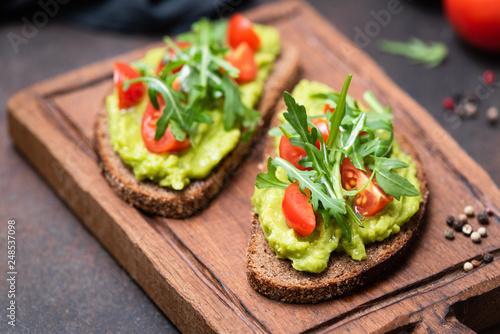 Fotografía Healthy vegan toast with avocado, tomato, arugula on wooden serving board, closeup view, horizontal image