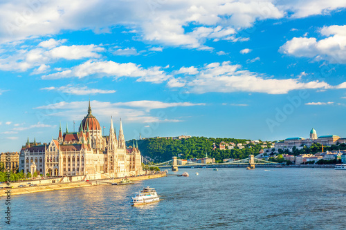Foto  Parliament and riverside in Budapest Hungary with sightseeing ships during summer sunny day with blue sky and clouds
