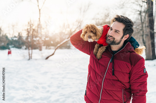Foto  Young adult enjoying a day in the park with his dog poodle