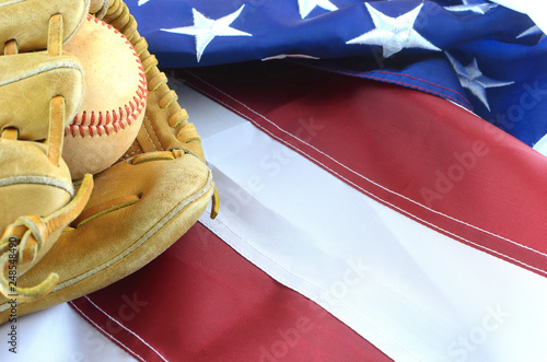 Fotografia, Obraz  Closeup of worn baseball and mitt on a US flag background, great for America's favorite pasttime