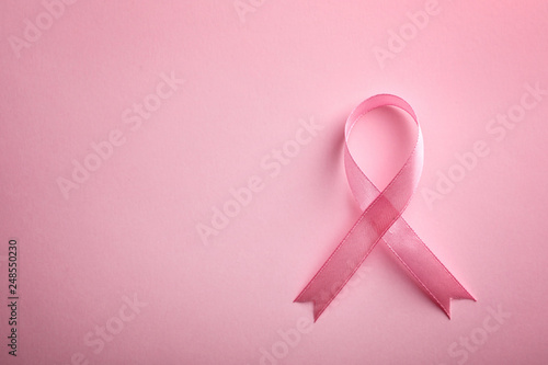 Fotomural  Pink ribbon on color background, top view with space for text
