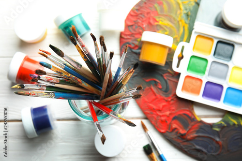 Foto  Glass jar with brushes, paints and palette on wooden background, top view