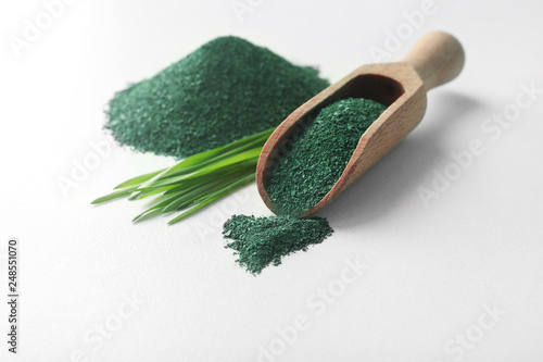 Composition with spirulina algae powder and grass isolated on white Wallpaper Mural