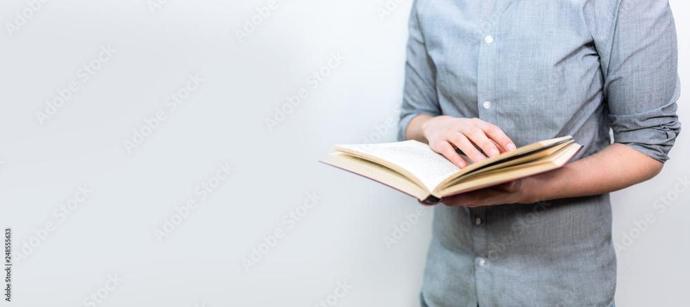 Fototapeta Junger Mensch mit grauem Hemd liest im geöffneten Buch als Banner Panorama
