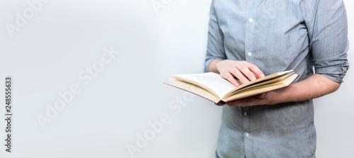 Photo  Junger Mensch mit grauem Hemd liest im geöffneten Buch als Banner Panorama