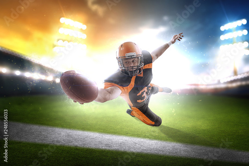 Fototapety, obrazy: American football player at the stadium in black and orange outfit.